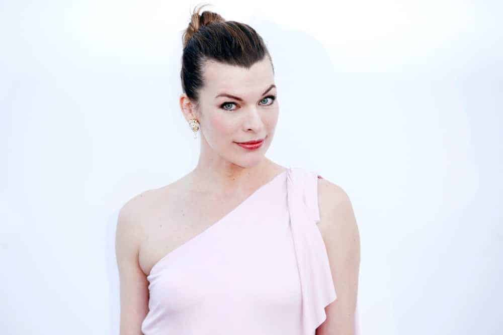 Milla Jovovich was at the amfAR Gala Cannes 2018 at Hotel du Cap-Eden-Roc on May 17, 2018, in Cap d'Antibes, France. She wore a white gown that she paired with her slicked-back bun hairstyle.
