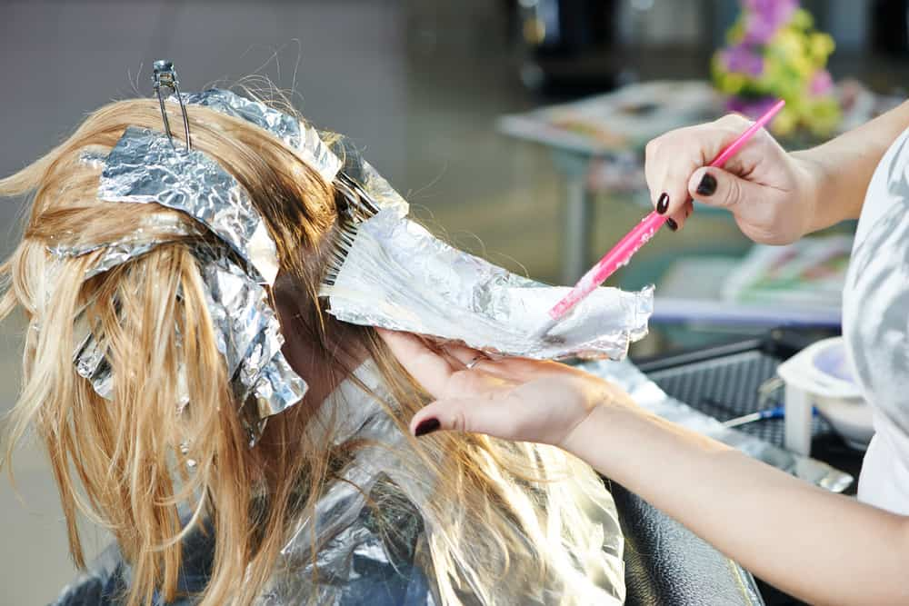 woman getting hair colored in hair salon