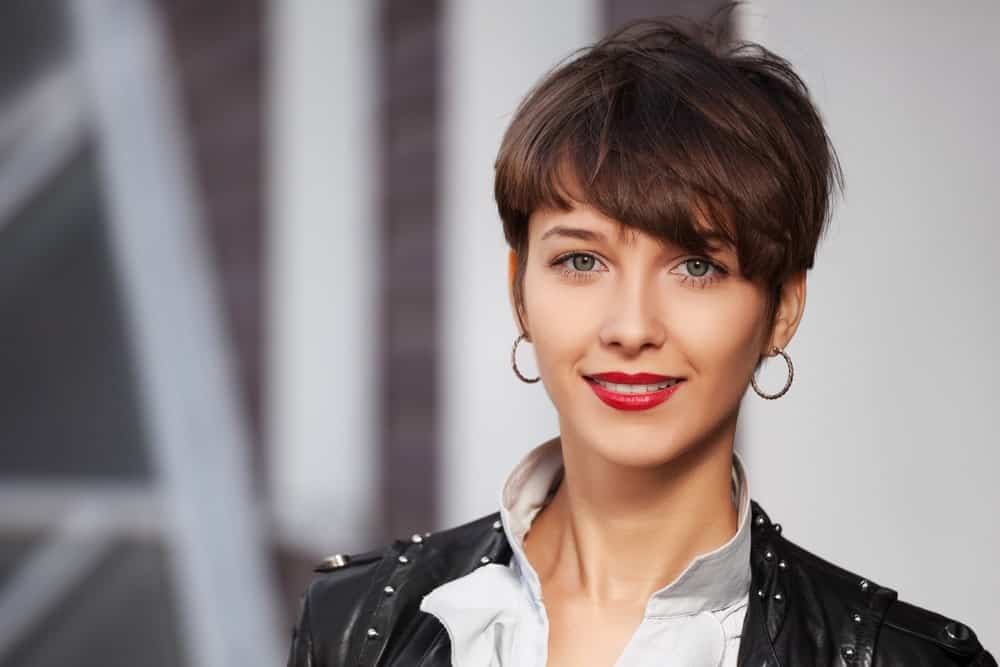 This young woman is sporting a classic pixie cut look. However, her side-swept bangs are a bit longer and almost touch her eye, giving her a super-hip look.