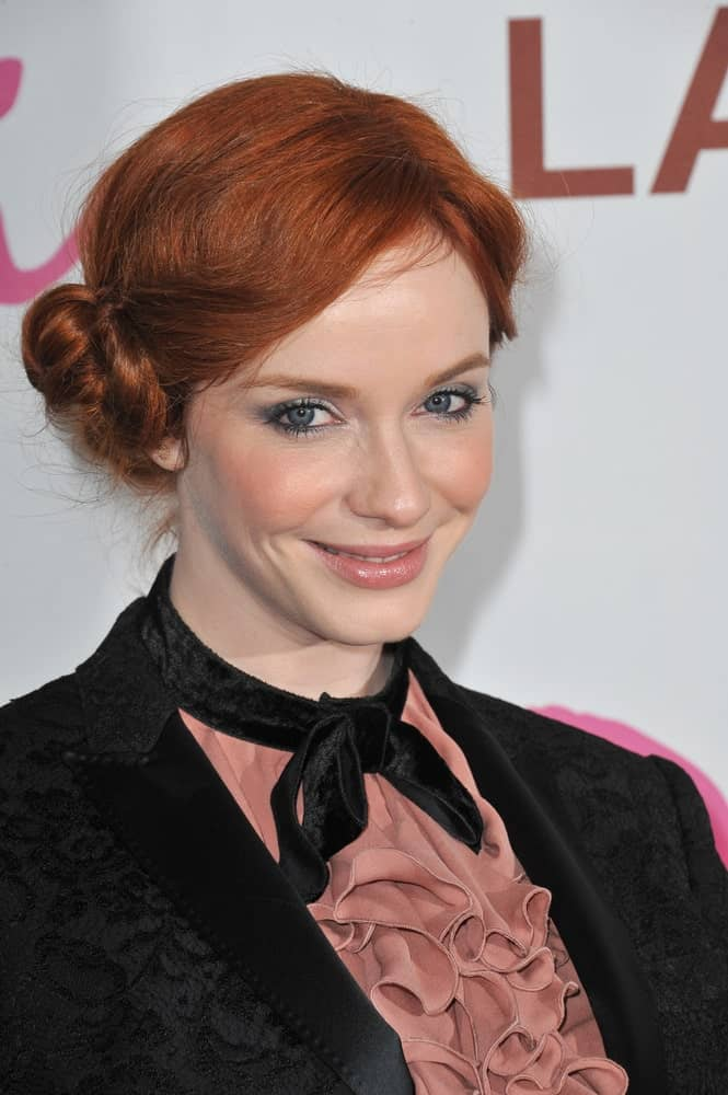 Christina Hendricks rocks her natural copper hues with a classy side bun and side swept bangs. It's a classy look while still giving off an effortless vibe, just like her charm.