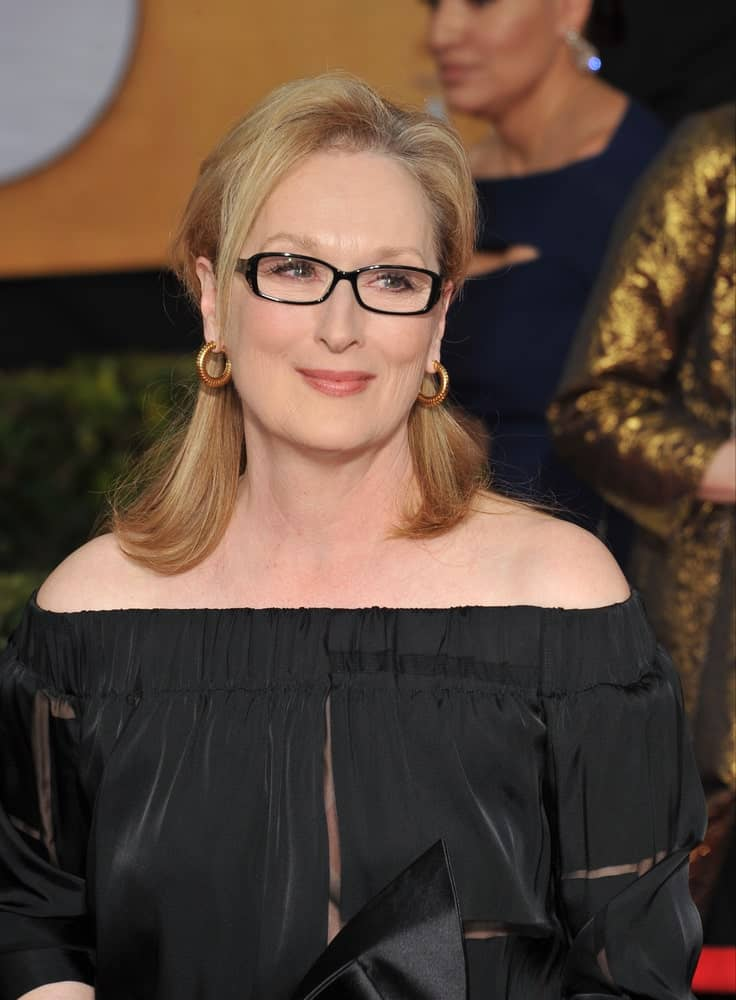 Modeled by Meryl Streep, this hairstyle is perfect for women over 50 who wish to show off their glasses in style. Shoulder-length hair secured at the middle in the back is the oldest hair trick in the book. The look is completed by a lock or two hanging loosely around the face to frame your glasses.
