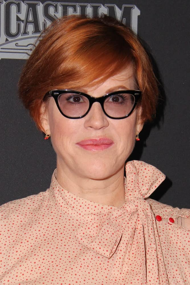 Molly Ringwald shows us how side swept bangs and a short bob are a great combination for copper haired folks who wear glasses.