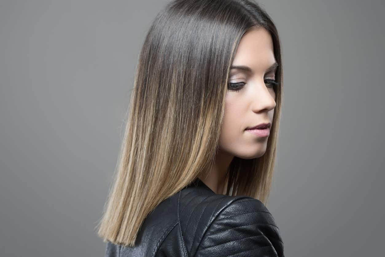 This stunning balayage starts from the young woman's natural dark hair and graduates into several shades of blond, giving her hair a nude ash blond look.