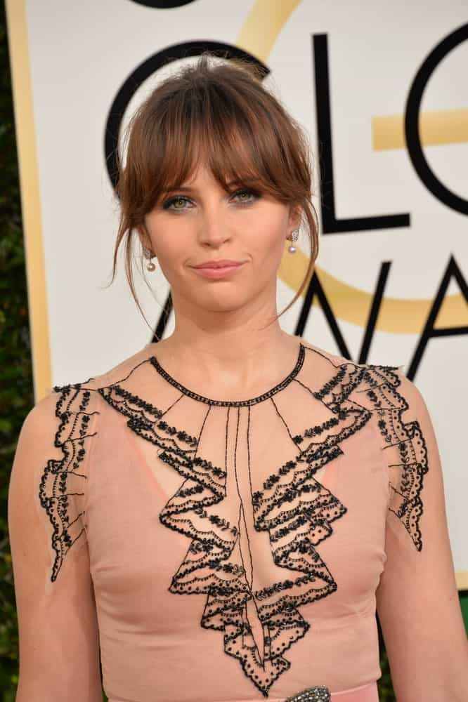 To add some drama to your classic bangs, blow them out and frame them with some errant wisps of longer hair, just like Felicity Jones. To bring focus to your bangs, pull your hair back in an updo.