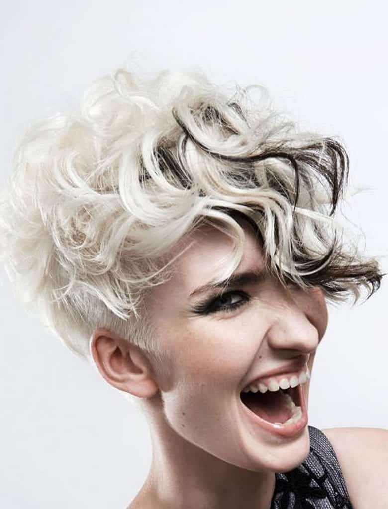 This wonderful hairstyle is super-short, almost shaved at the back. However, the top and front are comparatively quite long and can be styled into tousled, loose curls. Coupled with the black and silver hair color, this style has a very grunge look.