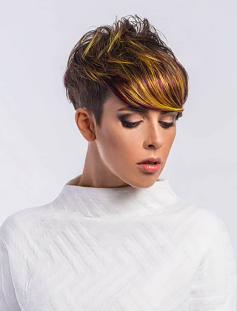 This haircut has long bangs on the front that reach the eyebrows. The back is quite short though and the top of the pixie cut is fluffed up to give a posh yet casual look.
