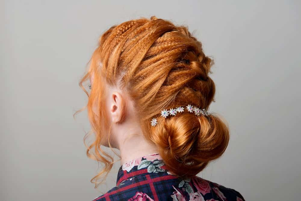 If your hair has dreadlocks, you could consider this beautifully textured updo that braids down the back of the neck and finished with a soft bun at the base.