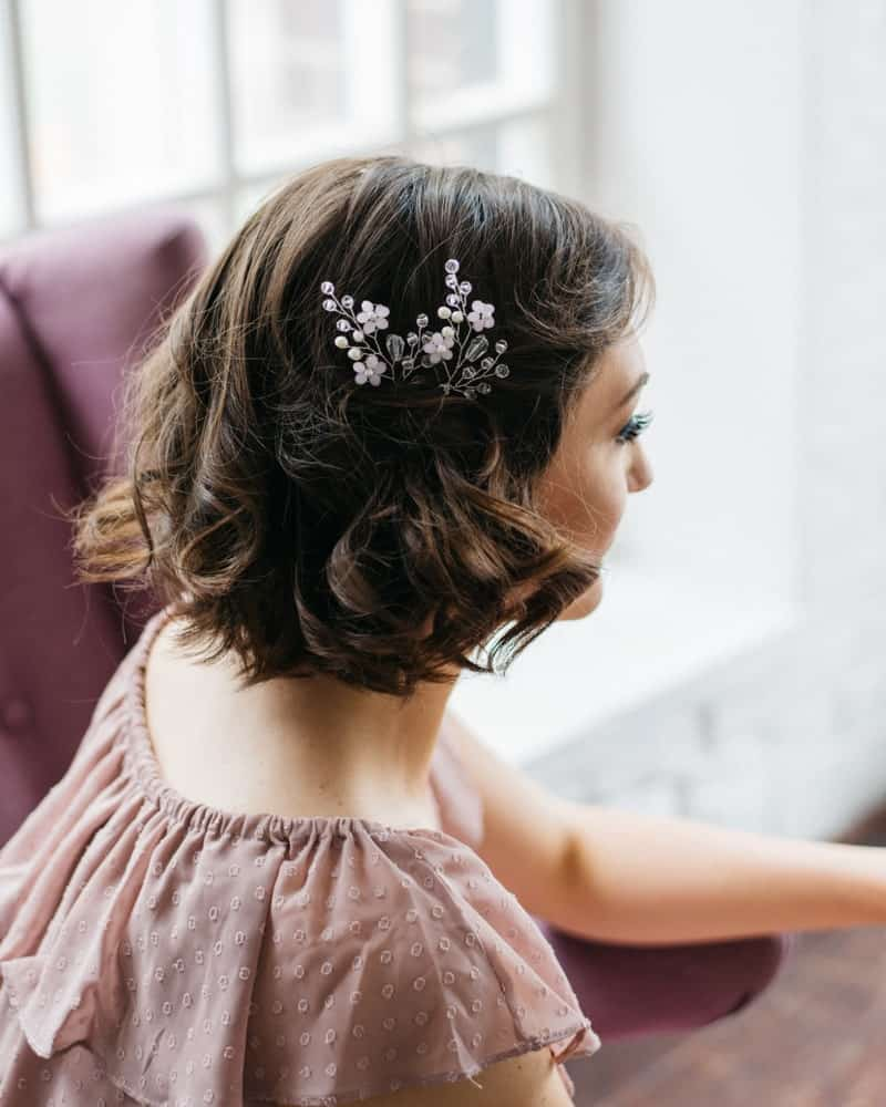 If you have short hair to begin with, you can dress it up with soft curls at the end and a stylish flower accessory.
