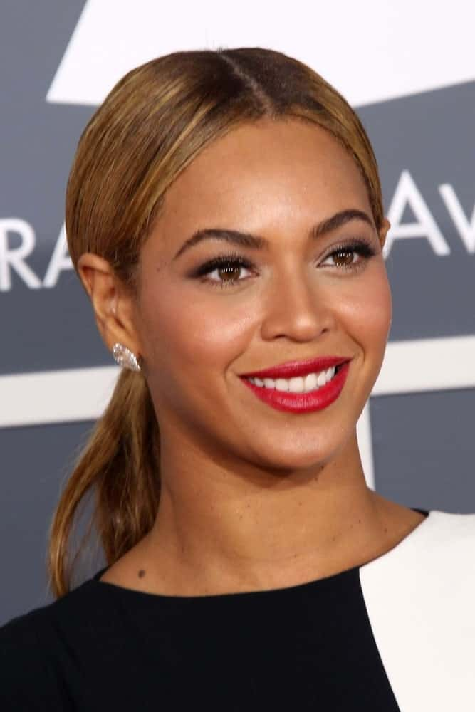 Beyonce rocks a middle parting here as well, but pulls her hair back into a ponytail so her earrings can shine. A great choice for keeping your face the main focus!