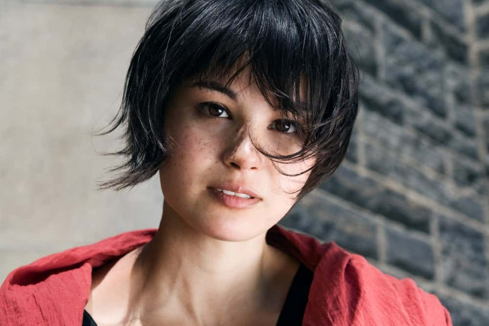 This pixie haircut is coupled by a few wisps of longer hair on either side. This variant of the pixie cut gives this young woman a youthful, playful look.