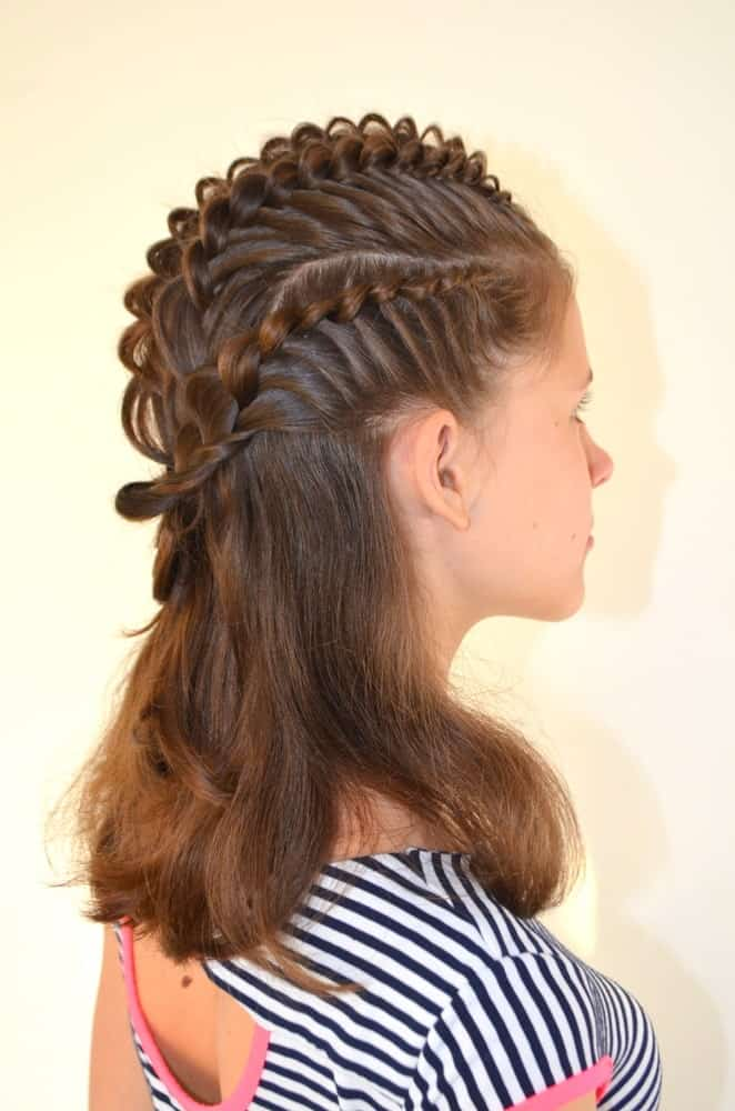 This hairstyle has tight French braids running along the side and top of the girls head. It adds a lot of height to the crown of the head and looks edgy and stylish.