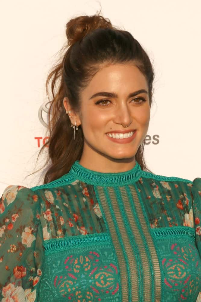 The actress sports a top bun at the crown of her head with messy waves. This is a great, easy hairstyle that works with any kind of hair length and most textures.