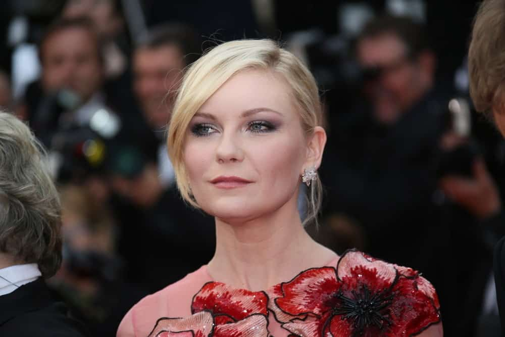If you have a layered haircut, you can create your bangs to suit the occasion. As Kirsten Dunst demonstrates, pull your hair back in a tight updo and swoop your longer front layer to the side of your face for a dramatic and posh effect. This removes the severity of the bun and gives a volumizing effect to your hair.