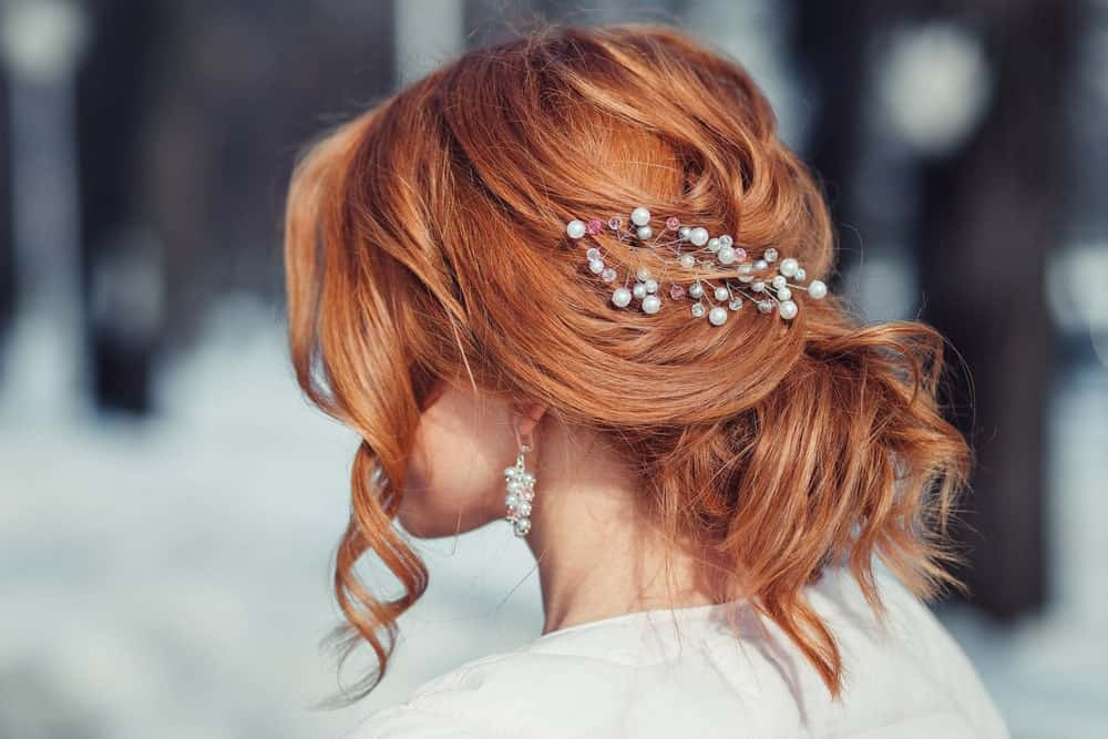 If you're looking for a more formal hairstyle, consider this twisted bun with soft curls framing the face and a hair accessory to top it off. Pearly white and gray accessories go great with copper hair.