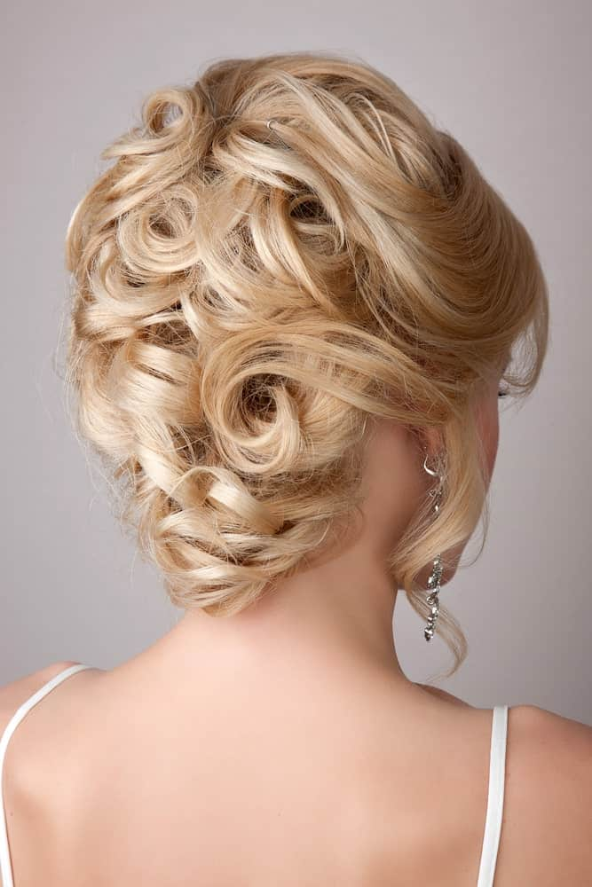 This gorgeous hairstyle mimics a rose bouquet. With lots of inwards twists and curls, this beautiful updo looks extremely flattering on every shade of blonde.