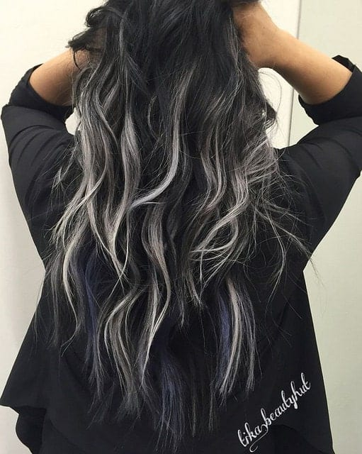 One of the biggest fashion trends these days is silver hair. This young woman has incorporated silver-blond balayage highlights in her naturally black wavy hair, giving her a very cool, uber-modern look.