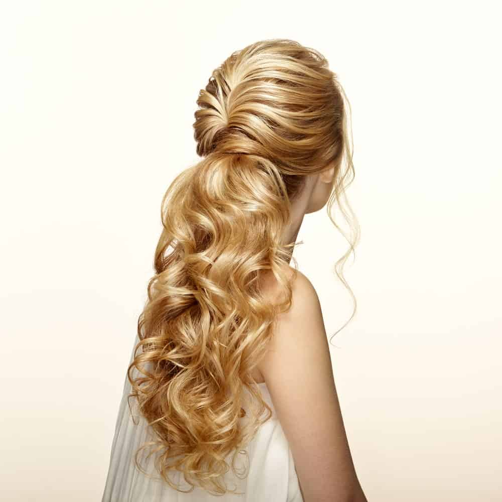 This half up, half down hairdo combines soft waves for the pinned top half of the hair with softly bunched curls on the bottom half for an intricate but beautiful hairdo. There is slight backcombing at the top to give some lift and volume to the hair and hold the waves in place. This is best done on longer hair so there is more space to play with it.