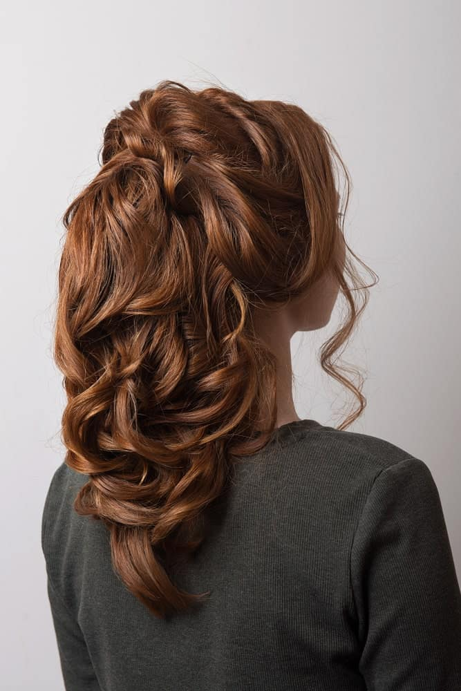 This hairstyle is a gorgeous option because it combines a little bit of everything. There are soft curly strands to frame the face, backcombing to add heights, pinned up twists for some interest, and gently cascading waves for a nice sleek finish.