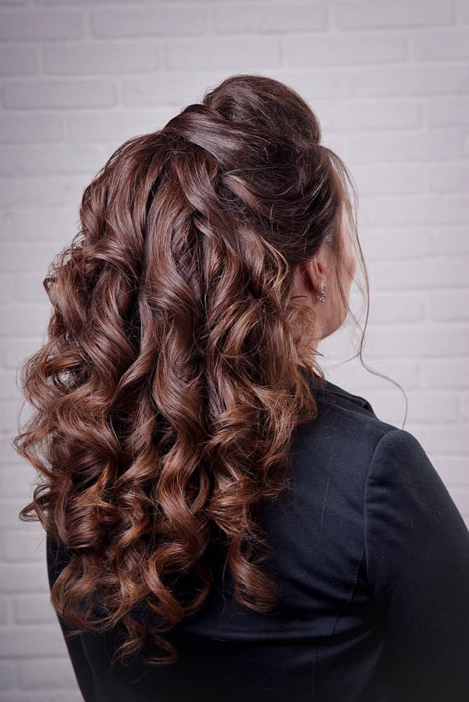 Another option for half up half down hairstyles is this sleek hairdo that keeps the backcombed bun simple but adds tons of volume with teased curls.
