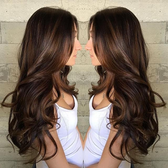 This yummy-looking balayage consists of dark chocolate brown hair with lighter caramel highlights. With the loose curls look, this balayage is giving this young woman's hair another dimension.