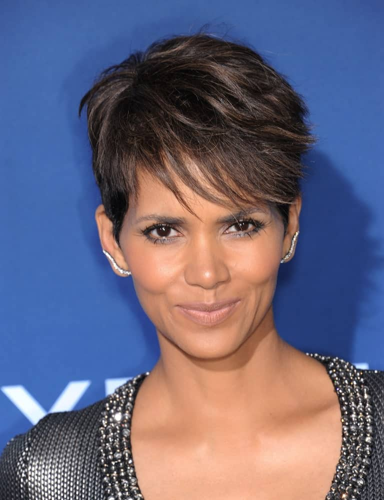 Halle Berry's textured and wispy pixie hair cut is all thanks to her beautiful naturally curly hair. The actress has kept her bangs long in the front and short on the sides for an edgy look.