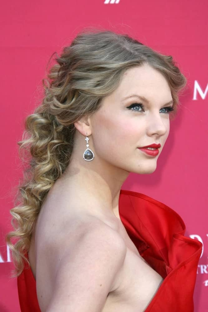 Taylor Swift adds a twist to a simple pinned back hairstyle by adding tight curls. It makes the hairdo seem more textured and more voluminous.