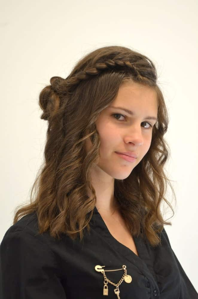 This youthful hairstyle uses the classic waterfall braid, but ends it with a twist by pinning up a small bun at the side of the head right above the ear. It works great with slightly curly hair because it will have more grip than silky straight locks.