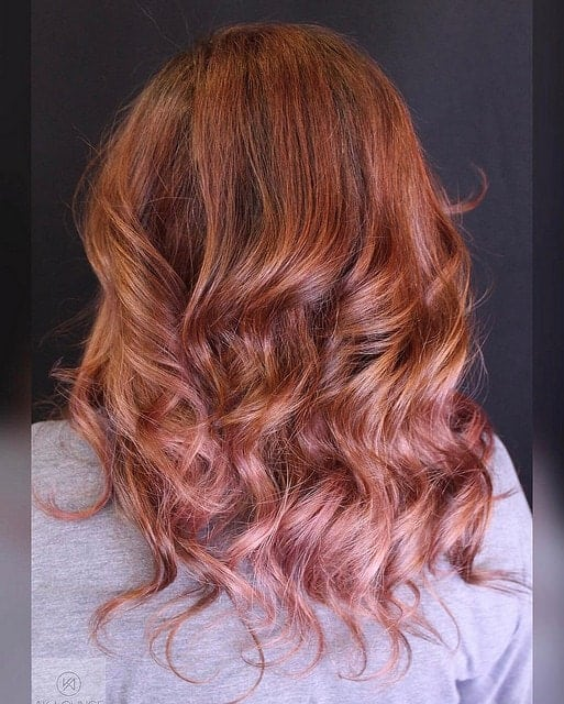 A very unique shade of red, this balayage incorporates the natural autumn red colors but also give a hint of strawberry pink to the end.