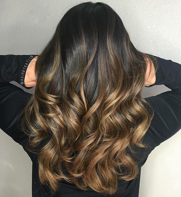 This young woman has created a dark blonde and caramel effect on her black hair. The stunning glossy gold and brown shades on her dark hair look like melted bronze has been poured over her tresses