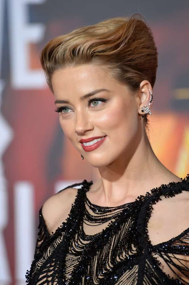 This angled, gravity defying hairstyle is one of our trend favorites. Stand apart from the crowd like Amber Heard does with an elegant, wavy angled updo.