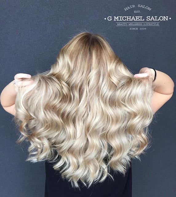The several hues of platinum, buttery yellow and sun-kissed yellow, coupled with the tousled locks, make this perfect beach bombshell balayage. This young woman looks ready to hit the sun, surf and sand.