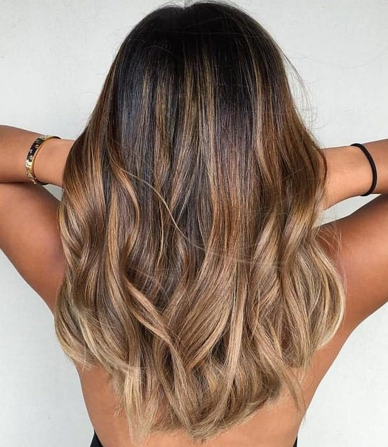 This balayage is made up of chestnut, caramel brown, sandy blond and ash blond shades. With her tanned skin, the highlights look like they have been naturally bleached by the sun.