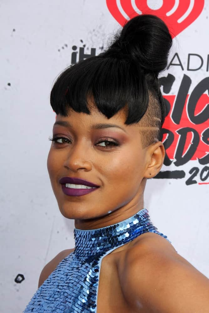 Keke Palmer is known for pulling off risqué looks. Her cool new hairstyle is achieved by shaving the sides of her head. The top and back part of the hair is pulled into a tight ballerina bun but the front part of her hair comprises of thick and pointed-cut bangs.