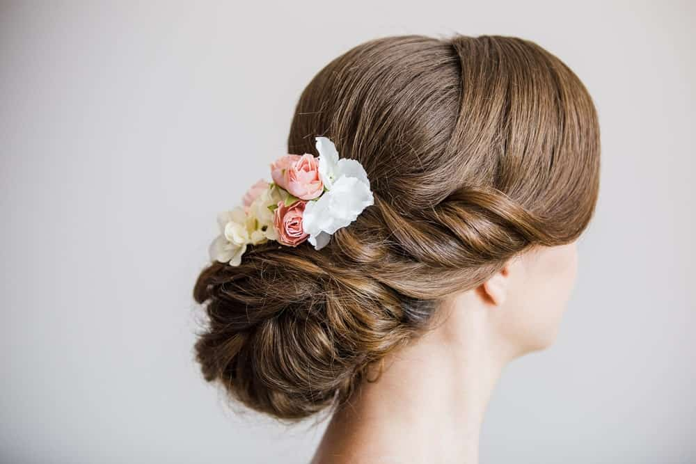 A side bun with flowers is never going to look bad. This particular hairstyle uses elegantly swept bangs with soft curling twists to complete the look.