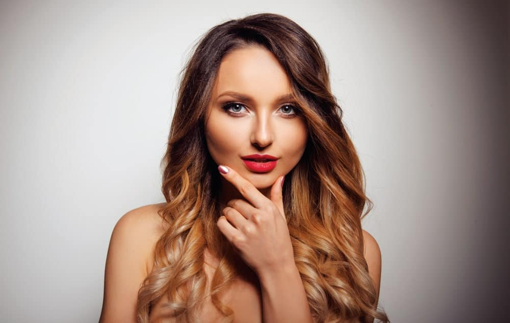 This young woman sports a balayage that graduates from a dark, rich caramel color to a golden honey and copper shade. It's a perfect look with long loose curls.