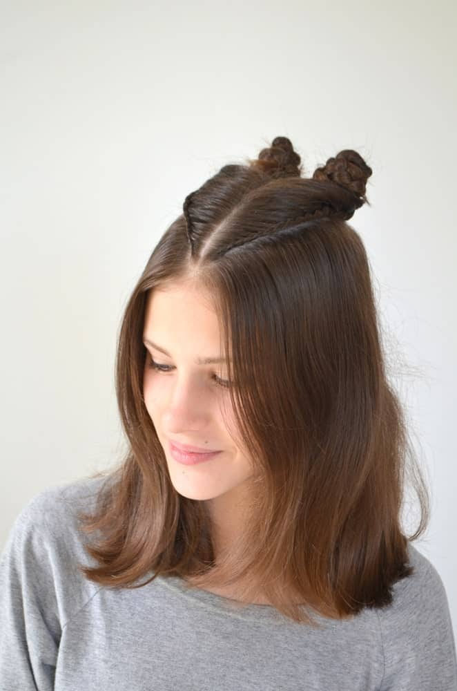 Adding a twist to the classic top knot, this hairstyle sweeps up the hair from the crown for two small top knots, leaving the rest of the hair flowing loose. It's trendy, simple, and easy to do yourself.