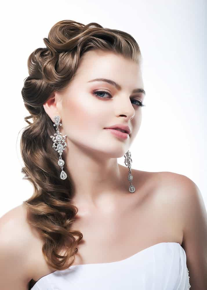 Though this may be a bridal hairdo, we think it will look absolutely stunning at a prom. The curls are more defined and elegantly bundled to the side for a soft finish that looks very old Hollywood.