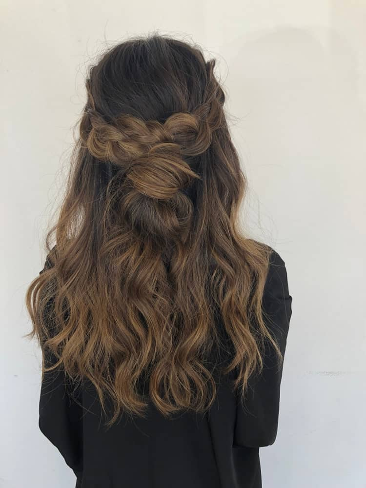 This beautiful balayage is a mix of very dark shades of brown. The crown braid styling highlights the gradient of colors in the woman's hair.