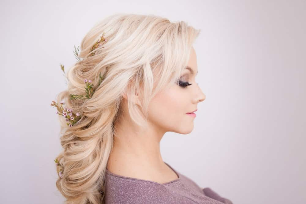 Soft curls are entwined with flowers to create this elegant, pretty hairdo. There's a little bit of backcombing at the crown where the hair is pinned back but the rest of the locks are gently curled into one another for a soft finish.