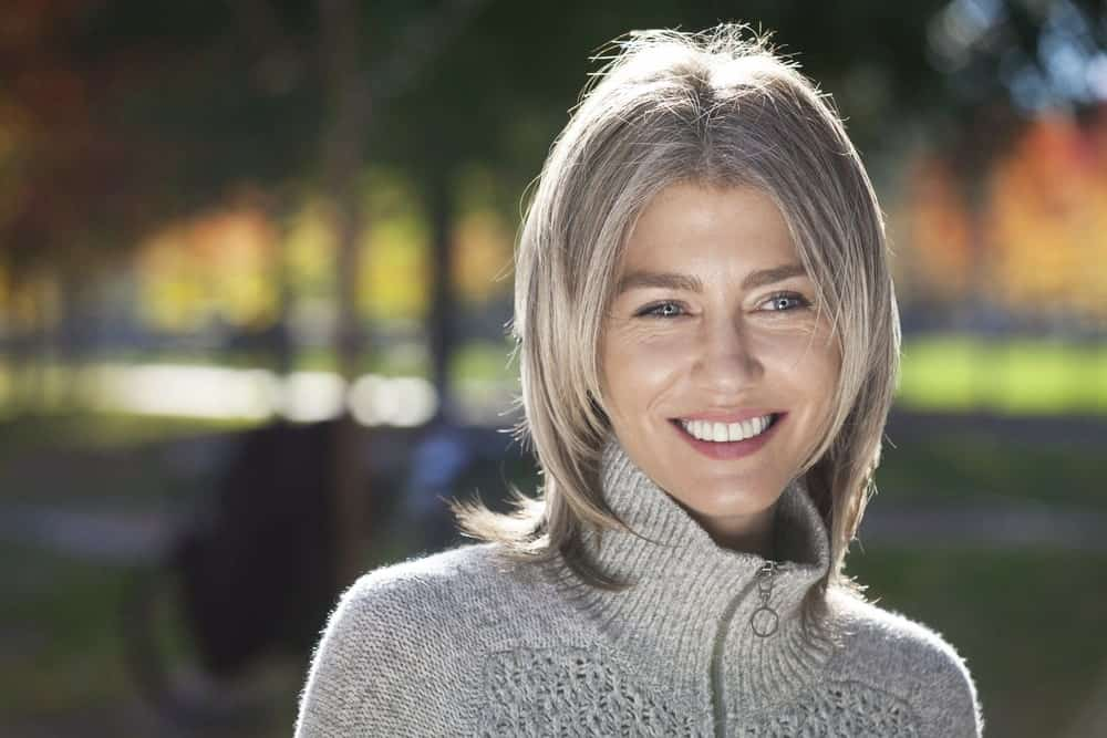 The color silver is not just for aging women; it looks great on young, fashion forward women as well. Take a look at this balayage with subtle silver highlights on ash blonde hair. The look makes this woman look so much younger.
