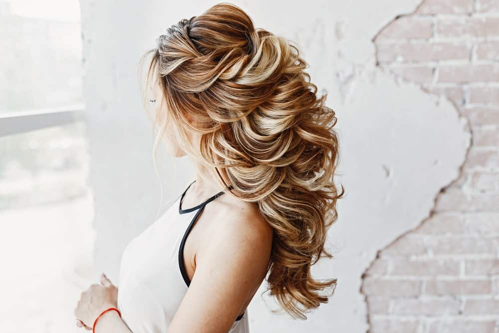 This hairstyle has tons of volume. With backcombing at the crowns and lots of voluminous curls, it adds height to any hairdo out there.