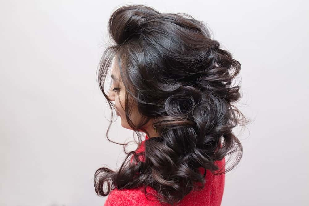 Gentle curls are the star of this hairdo. Sweeping the curls to one side gives an elegant, softer look.