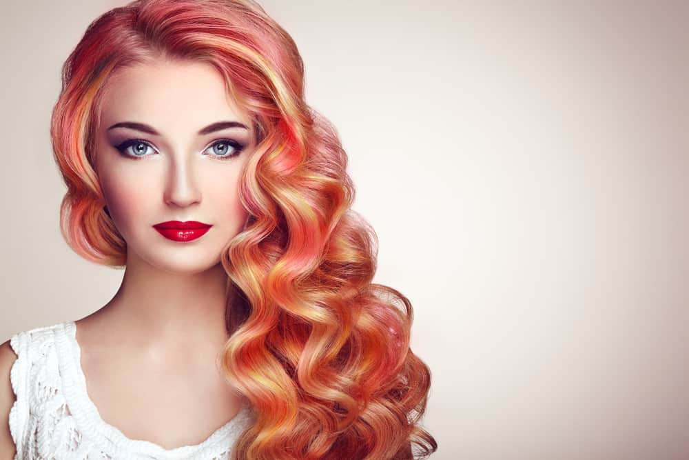 A model with red and pink curly hairstyle