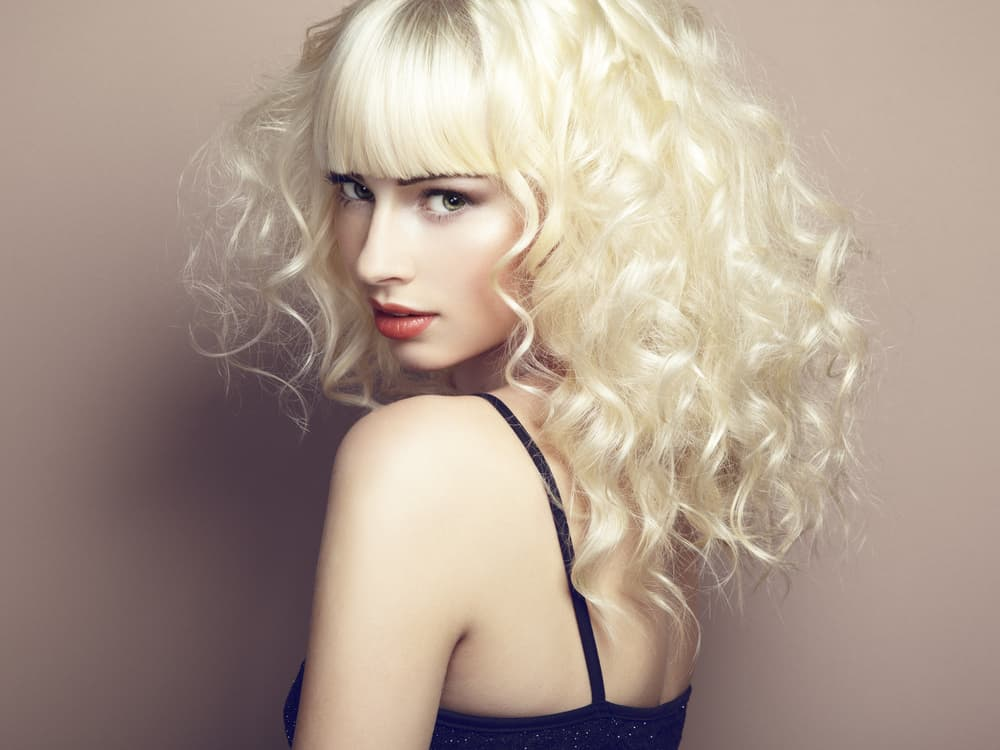 A model with platinum blond curly hair with bangs