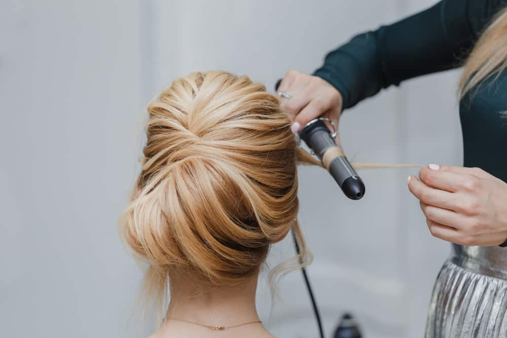 A model getting her hair done in an elaborate French twist