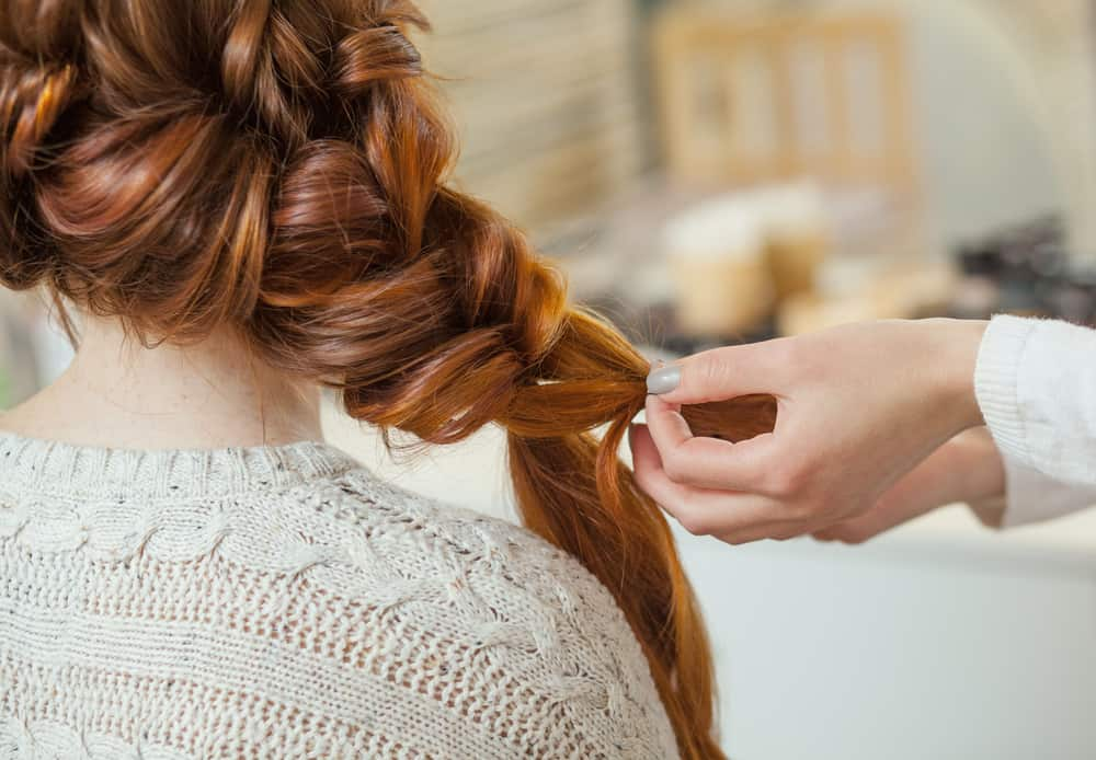 A woman styling a messy French braid on a redhead