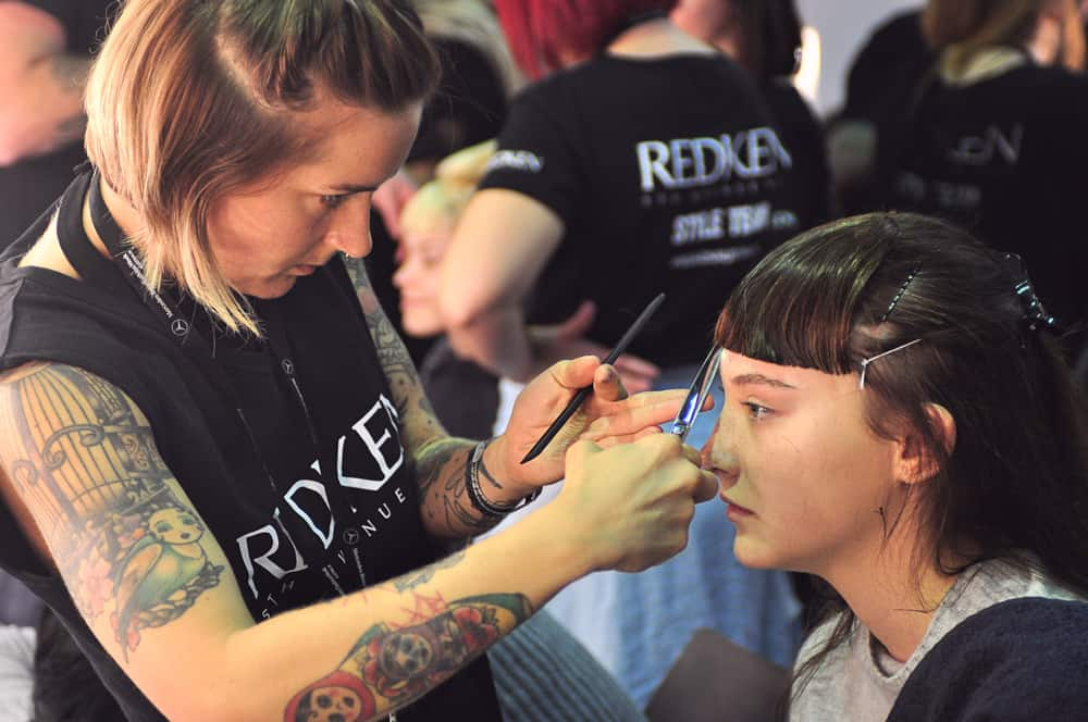 A Redken hair stylist cutting a model's hair backstage at Mercedes Benz Fashion Week