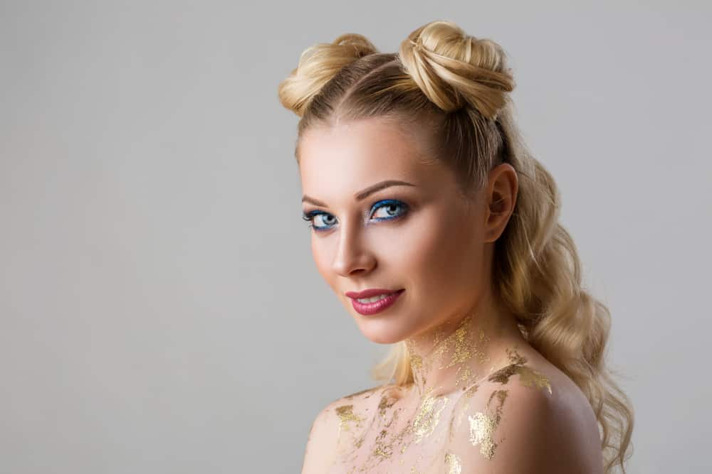 A young woman with side buns in her long curly blond hair