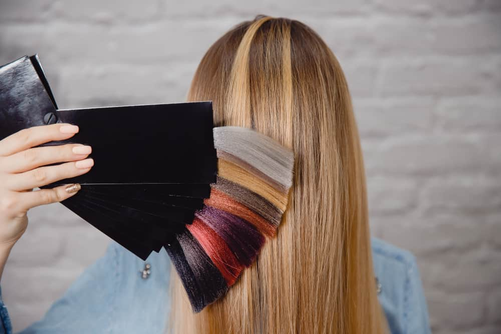 A hair stylist showing a palette of hair color behind a client's head