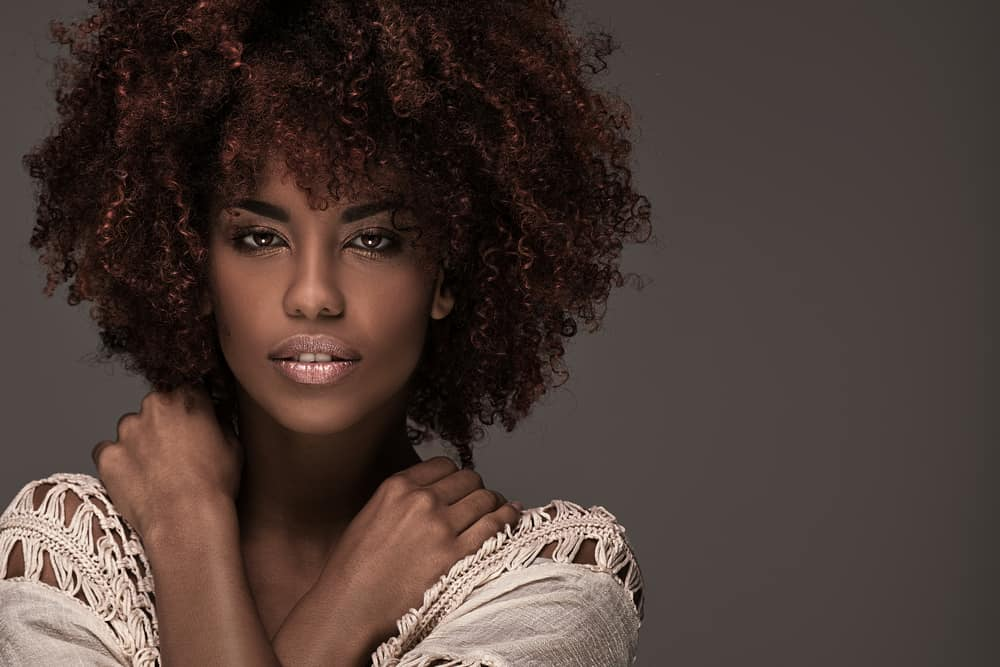 A model rocking an afro hairstyle and glamour makeup